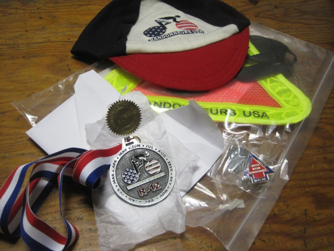 To the victor go the spoils... wool cap with RUSA logo, RUSA-branded reflecto triangle, dart lapel pin... and R-12 medal!